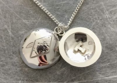 Silver locket opened with initial T inside