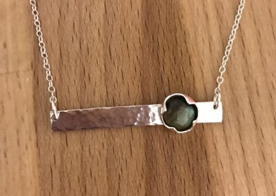 Silver bar pendant set with a garnet